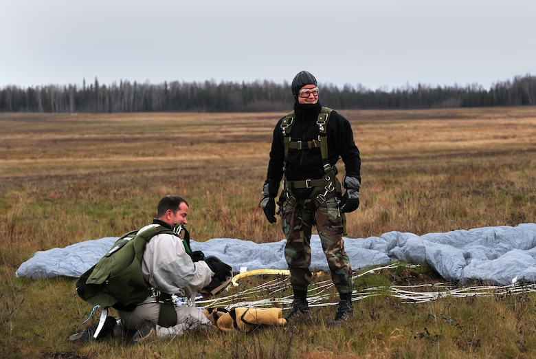 FORT RICHARDSON, Alaska -- 1st Lt. John Romspert and Senior Airman Don Lacy wrap up their landing and gear after a tandem jump during pararescuemen training at Malamute drop zone Oct. 21. Being one to pack parachutes for pararescuemen, Lacy wanted to experience how the parachute worked in action. Romspert is a combat rescue pilot with the 212th Rescue Squadron and Lacy is an aircrew flight equipment specialist with the 176 Operational Support Flight both at Kulis Air National Guard Base, Alaska. (U.S. Air Force photo/Senior Airman Cynthia Spalding)