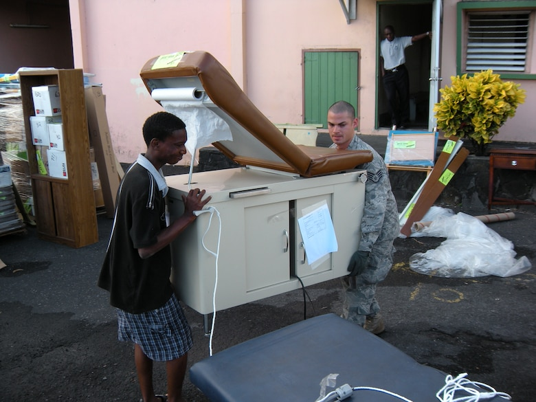 Staff Sgt. Daniel Osorio, 52nd Airlift Squadron C-130 Hercules crew chief, helps a local man move an examination table during an Oct. 30 delivery of humanitarian supplies to the Caribbean island of St. Vincent. The supplies, donated by the Wausau, Wis. based Good News Project, included hospital and mental health supplies as well as desks, paper and school supplies to various locations on the island. The Air Force Reserve aircraft transported the supplies under the Denton Amendment, which authorizes U.S. military aircraft via Congress to airlift humanitarian supplies based on space availability and other factors. Sergeant Osorio is an Active Duty Airman associated with the AF Reserve's 302nd Airlift Wing based at Peterson Air Force Base, Colo. (U.S. Air Force photo/Staff Sgt. Stephen J. Collier)