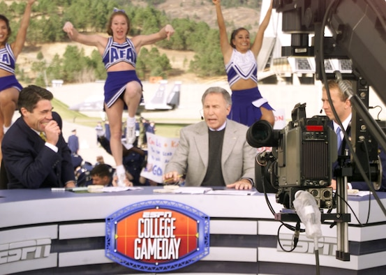 "ESPN College GameDay host Chris Fowler, left, cracks up at the antics going on behind the set, while cohost Lee Corso is on-camera explaining why fans should ""wait a minute"" during their first live broadcast from the Academy Nov. 2, 2001. ESPN College GameDay returns to the Air Force Academy Nov. 7, and will broadcast live from the Terrazzo before for the Air Force-Army football game. The Academy cheerleaders in this photo are, left to right: Karen Jelke, Sabrina Kingston and Bernadette Lavarrada-Perez. (U.S. Air Force photo/John Van Winkle)"