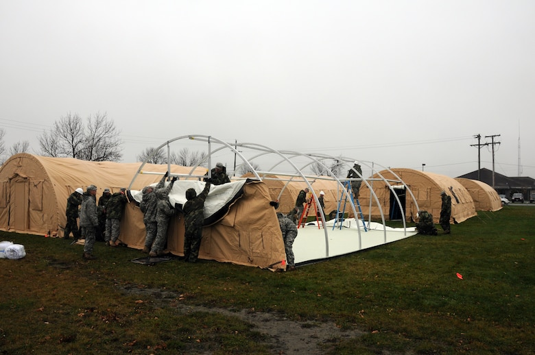 Niagara ramps up for Vigilant Guard. Civil engineers from the 107th Airlift Wing, work together with members from A Company 642nd, Army National Guard to construct a tent city. The work crew will erect 32 Rapid Deployment System shelters that will house up to 300 military responders. The RDS are highly mobile systems designed to be self contained temporary housing.  Each RDS comes complete with all necessary equipment to safely set up each shelter in a matter of a few hours. USAF Photo/Staff Sgt. Peter Dean.