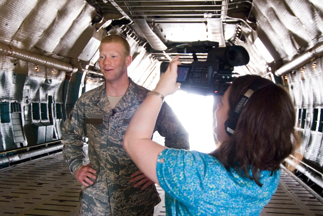 Hannah Maxwell, a production assistant for West Virginia University's Television Productions, documents an interview for a recruiting video for WVU with Senior Airman Nathan Sisler in a C-5 aircraft at the 167th Airlift Wing, Martinsburg, West Virginia, on August 27, 2009. Sisler, a WVU senior and a West Virginia Airman of the Year recipient for 2009, was chosen to be featured in the video because of his leadership qualities according to Kelly Heasley, special projects prouducer for WVU's Television Productions. (U.S. Air Force Photo by Emily Beightol-Deyerle)