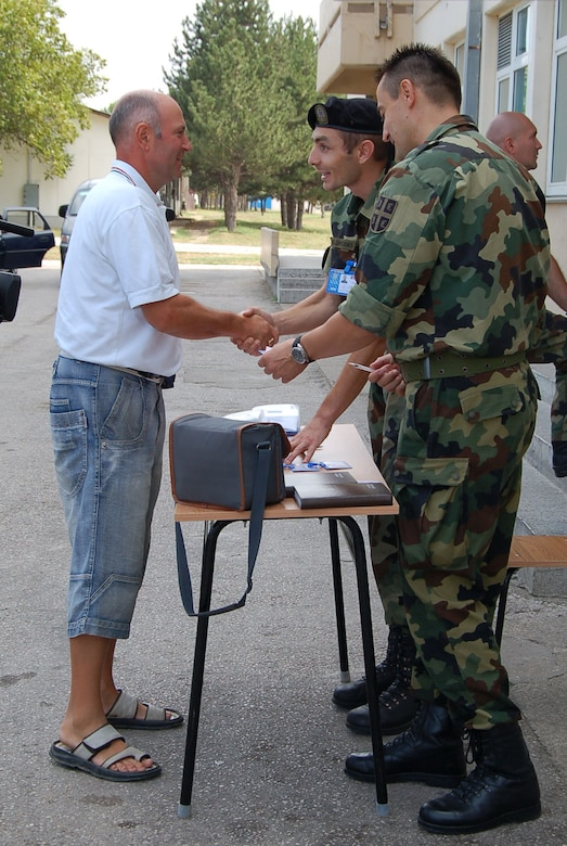 NIS, Serbia – Senior Sergeant Milos Miladinovic, Serbian Armed Forces Force Protection (left), shakes hands with a representative of the Republic of Macedonia Aug. 31 as a fellow SAF member stands by during in-processing into the military medical training exercise in Central and Eastern Europe, better known as MEDCEUR 2009, in Nis, Serbia. (U.S. Air Force photo/Senior Airman Kali L. Gradishar)