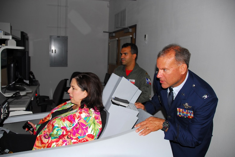 Col. Kenneth Nereson, commander of the Texas Air National Guard's 149th Fighter Wing, watches State Sen. Leticia Van de Putte, of San Antonio, simulate flight in an F-16 trainer at Lackland Air Force Base, Texas, on August 28, 2009. (U.S. Air Force photo/Staff Sgt Phil Fountain)