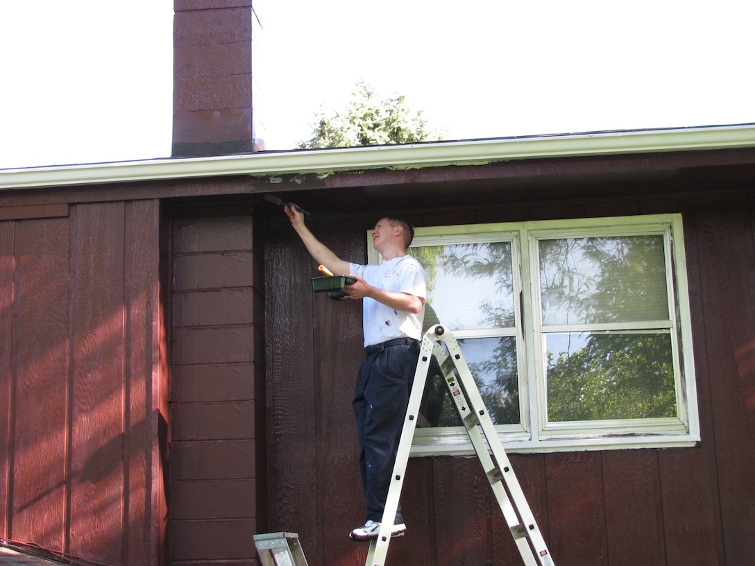 BELLEVUE, Neb. -- Maj. Christopher A. Schwartz, 45th Reconnaissance Squadron, paints the underside of the roof of a house in Bellevue, Neb. Aug. 22 during the 21st annual Brush Up Nebraska Paint-A-Thon. The annual event started in Sept. 1989, since then more than 2,000 homes have been painted. U.S. Air Force Photo by Master Sgt. Kevin Pawlik