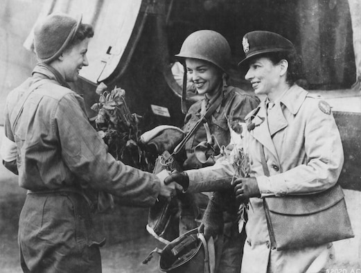 Two of the first flight nurses to make evacuation flights into Normandy after D-Day, Lts. Suella Bernard (left) and Marijean Brown (center) are greeted by Lt. Foster, their head nurse. They are holding poppies they brought back from the Normandy beachhead. (U.S. Air Force photo)