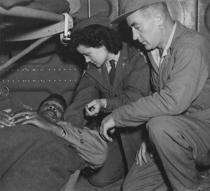 A C-47 air evacuation team from the 803rd Air Evacuation Transportation Squadron, Lt. Pauline Curry and Tech. Sgt. Lewis Marker, check a patient on a flight over India. (U.S. Air Force photo)