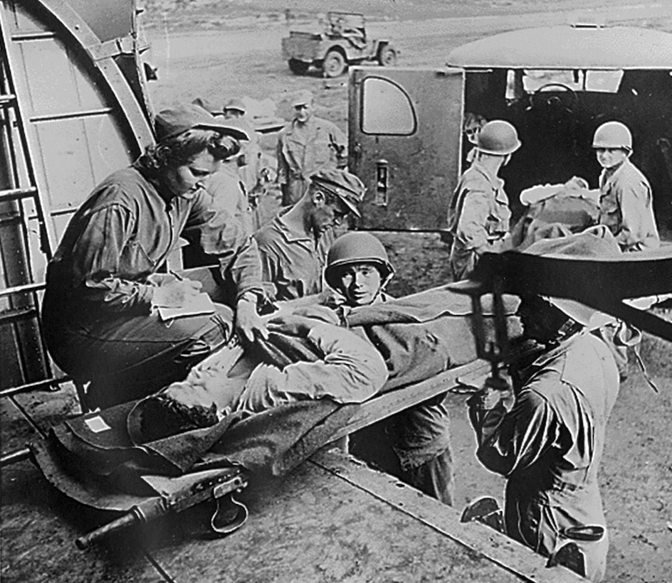 Flight nurse Lt. Mae Olson takes the name of a wounded American soldier being placed aboard a C-47 for air evacuation from Guadalcanal in 1943. Due to such factors as noise, vibration, and the risk of hypoxia, only very stable patients were able to be transported at this time. (U.S. Air Force photo)