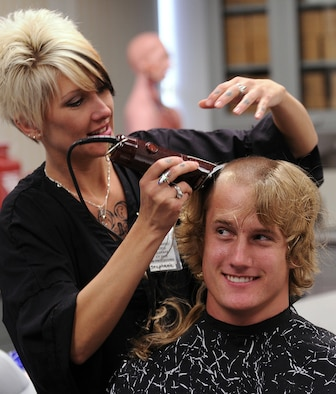 Air Force Academy Basic Cadet Logan Mitchell gets his hair cut on inprocessing day June 25, 2009.