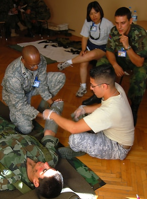 NIS, Serbia – Capt. Radcliffe Myers, 86th Medical Operations Squadron clinical nurse at Ramstein Air Base, Germany; and Staff Sgt. Brayan Jimenez, 86th Aerospace Medicine Squadron medic, also from Ramstein AB; practice applying dressing and bandages to a simulated burn victim played by Stefan Krstic, Serbian Armed Forces soldier, while Capt. Roslyn Thomas, Landstuhl Regional Medical Center nurse in Landstuhl, Germany, and Senior Sgt. Nenad Stevanovic, SAF medical support commander, discuss the process during a military medical training exercise in Central and Eastern Europe, or MEDCEUR 2009, trauma nursing training course taught by members of SAF medics Sept. 4. (U.S. Air Force photo/Senior Airman Kali L. Gradishar)