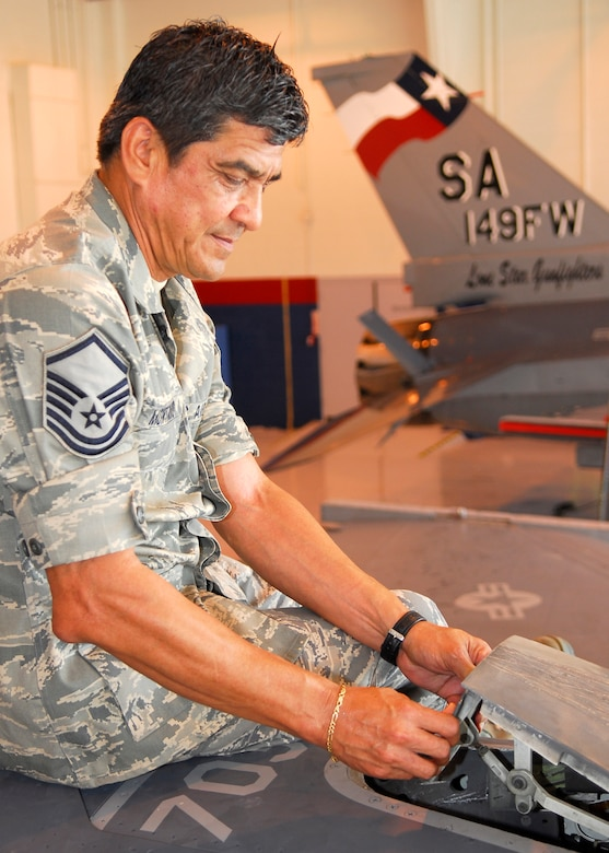 Master Sgt. Edward Montalvo of Tecumseh, Michigan, a fuels system technician assigned to the Texas Air National Guard's 149th Fighter Wing, looks at the F-16 in-flight refueling door that leads to the coil induction plate at Lackland Air Force Base, Texas on Aug. 27, 2009. (U.S. Air Force photo by Senior Master Sgt. Mike Arellano)(RELEASED).
