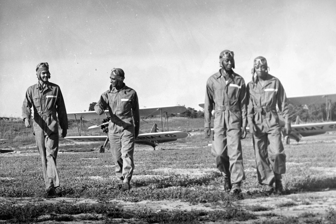 Tuskegee students talk about flying their Stearman biplanes. At far left is Capt. Benjamin O. Davis Jr., the squadron commander. (U.S. Air Force photo)