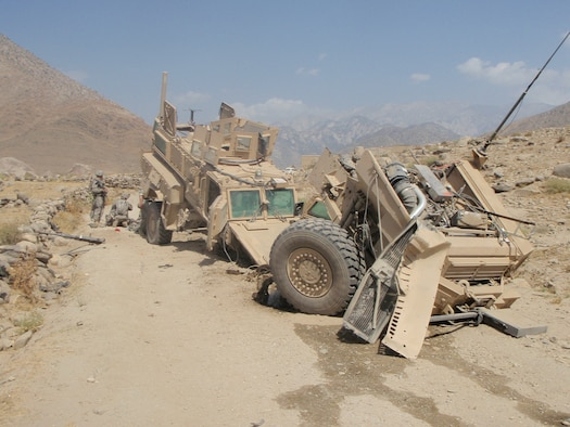 The Mine Resistant Ambush Protected vehicle lies in disarray after being struck by an improvised explosive device while returning from a humanitarian mission to give medical attention to women and children at a small Afghan village Aug. 12. Airman Dowdy was able to perform life-saving aid to injured Soldiers who were also on the convoy mission. (U.S. Air Force photo by Airman 1st Class Destiney Dowdy)