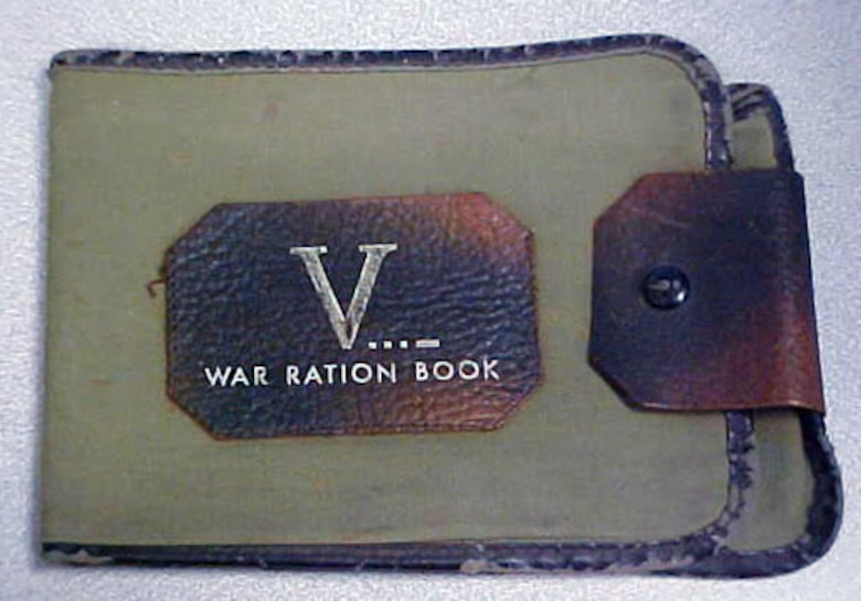 This olive drab cloth and brown leather wallet-style book was used for holding war rations. (U.S. Air Force photo)