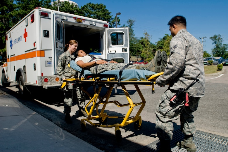KUNSAN AIR BASE, Republic of Korea --Tech. Sgt. Samantha Mosher and Senior Airman John Reyes, 8th Medical Operations Squadron, lift a gurney with Senior Airman Ktreese Rodriguez as a simulated patient Sept. 10. Sergeant Mosher and Airman Reyes are emergency medical technician (EMT) qualified aerospace medical technicians assigned to ambulance services. Ambulance services primary duties are to respond to 911 calls, in-flight emergencies and sick call. (U.S. Air Force photo/ Senior Airman Jonathan Steffen)