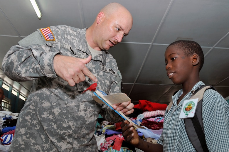 Command Sgt. Maj. Lynward Hall, with the 878th Engineer Battalion, Georgia Army National Guard, shows a Guyanese boy how to wind up a rubber-band powered airplane at the Joshua's Place Orphanage Sept. 9, 2009. Hall's battalion brought 32 duffel bags of toys and clothes and over $3,800 in donated items to the orphanage. (U.S. Air Force photo by Airman 1st Class Perry Aston) (Released)