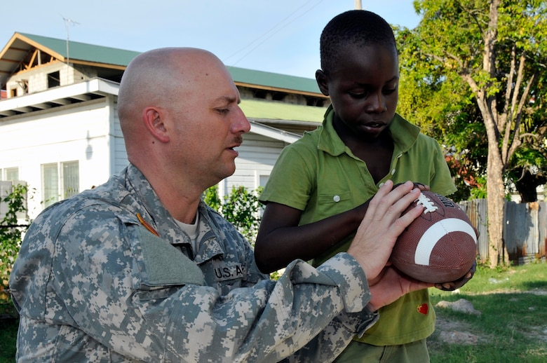 Command Sgt. Maj. Lynward Hall, with the 878th Engineer Battalion, Georgia Army National Guard, shows a Guyanese boy how to throw a football at the Joshua's Place Orphanage Sept. 9, 2009. Hall's battalion brought 32 duffel bags of toys and clothes and over $3,800 in donated items to the orphanage. (U.S. Air Force photo by Airman 1st Class Perry Aston) (Released)