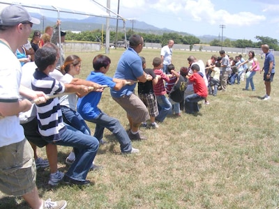 """SOTO CANO AIR BASE, Honduras — Local children and volunteers play tug-of-war during the Joint Task Force-Bravo's """"kid's day"""" Sept. 10 near the base soccer field. More than 100 children from local orphanages were transported to base for the event. The children participated in a variety of events the volunteers organized including a HH-60 Blackhawk static display, military working dog demonstration and fire truck display. The children also got to participate in soccer, kickball and a water balloon toss. A free lunch was also served and the children were given a """"goodie"""" bag containing small toys and candy as the left base (U.S. Air Force photo/Martin Chahin)."""
