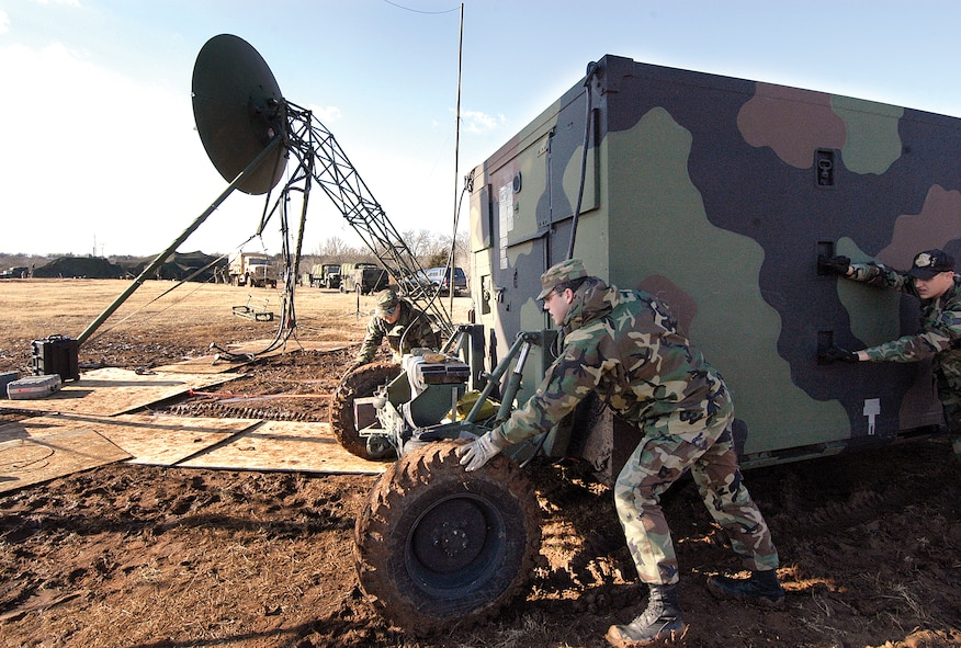 Airmen from the 3rd Combat Communications Group move a TRC-170 through the mud into position at the Glenwood Training Area during a 2008 joint exercise with the Army.  Fort Sill Soldiers set up in the distance. (Air Force photo by Margo Wright)