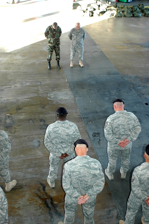 Members of the 162nd Fighter Wing at Tucson International Airport share a moment of silence in the base fire station to remember the Sept. 11, 2001, terrorist attacks on the United States exactly eight years after the fateful day. Chaplain (Maj.) Mike Martinez, upper right, and Senior Master Sgt. Shane Clark, base fire chief, led the wing in a prayer for all the lives lost and the families affected by the attacks. (Air National Guard photo by Maj. Gabe Johnson)