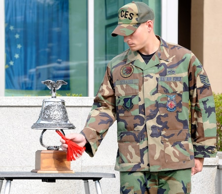 Staff Sgt. William Strauss rings a bell in remembrance of those who died, and whose lives were forever changed because of the Sept. 11, 2001 attacks. At 9:11 a.m., Sept. 11, members of Team Osan gathered in remember of the events and also pay tribute to the men and women of the U.S. Armed Forces who serve. (U.S. Air Force photo/Senior Airman Stephenie Wade)