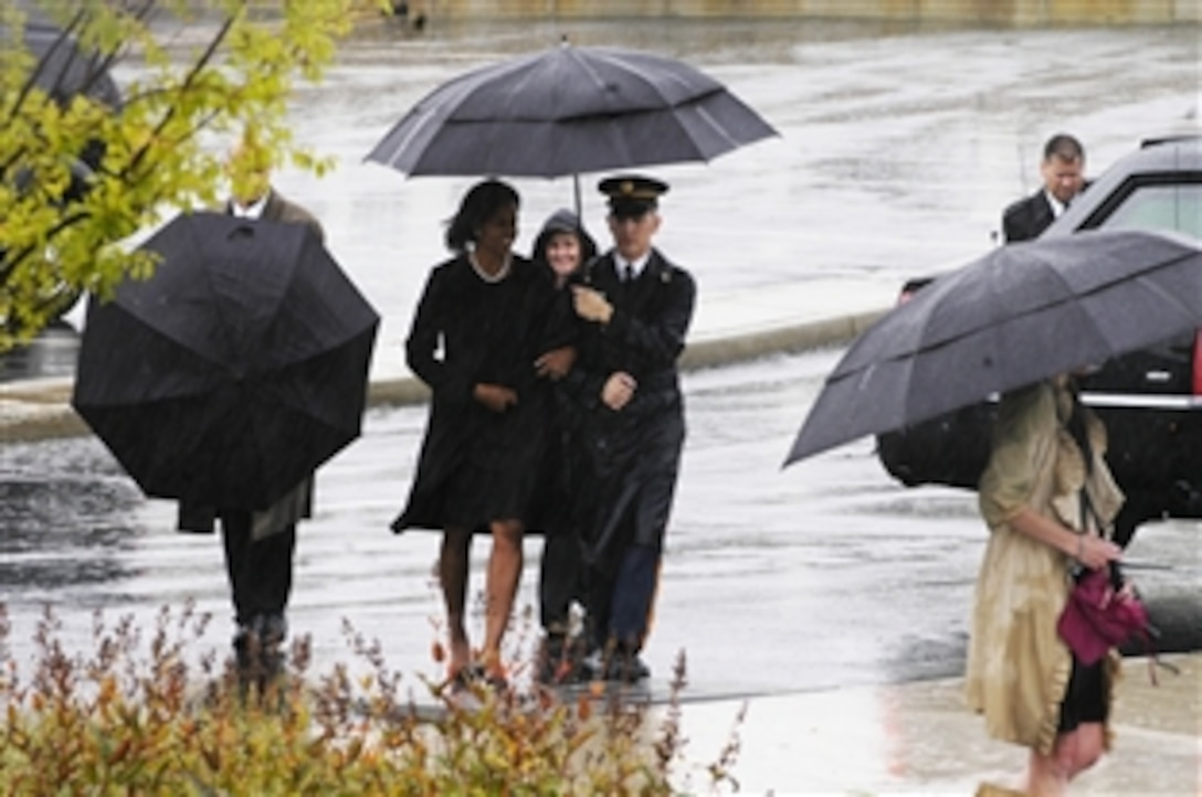 A soldier escorts first lady Michelle Obama from the motorcade to the Pentagon Memorial just before the 9/11 Remembrance ceremony Sept. 11, 2009. President Barack Obama, Defense Secretary Robert M. Gates and Adm. Mike Mullen, chairman of the Joint Chiefs of Staff, spoke at the event to families of the victims at the Pentagon.