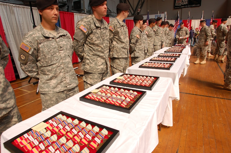 Army soldiers stand by, keeping watch over the medals to be handed out at the Freedom Salute Ceremony held at the William A. O'Neil Armory in Hartford, Conn.  Aug. 16, 2009. The ceremony served as the official welcome home for three units: the 103rd Air Control Squadron, the 1109th Aviation Classification Repair Activity Depot, and Detachment 2, Company I/185th Aviation Regiment. (U.S. Air Force photo by Tech. Sgt. Joshua Mead)