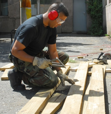 Tech. Sgt. Michael Meras of the 149th Civil Engineer (CEs) Squadron checks measurements on a two-by-six that will become part of a bench seat. He and others refurbished benches along a garden wall at a nursery in Yerevan, Armenia, during the first two weeks of August. Forty-five CEs and four other Air National Guardsmen from the 149th Fighter Wing, at Lackland Air Force Base, San Antonio, Texas deployed to Yerevan to complete an Expeditionary Medical Service facility and work on humanitarian assistance projects. (Texas Military Forces photo by Tech. Sgt. Rene Castillo)