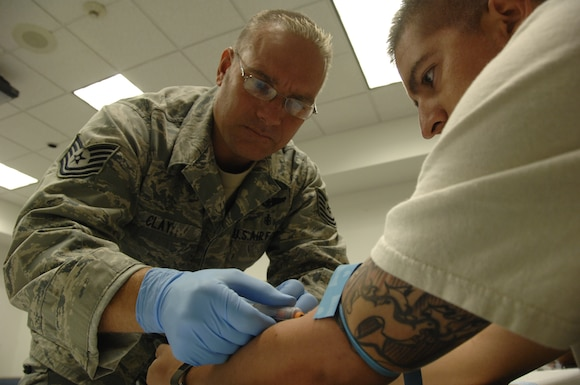Tech. Sgt. Franklin Clay, a medical technician from the 129th Medical Group, draws blood from Staff Sgt. Ernesto Godinez, an HH-60G Pave Hawk helicopter crew chief,  during a routine redeployment inproccessing at Moffett Federal Airfield, Calif., Sept. 9.  Sergeant Godinez returned from a four-month deployment to Afghanistan. (Air National Guard photo by Tech. Sgt. Ray Aquino)