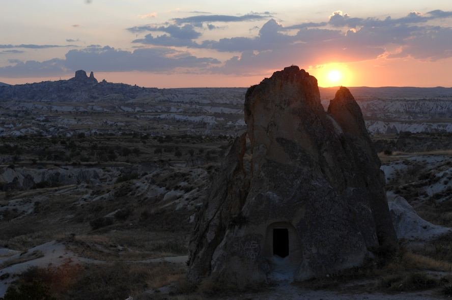The sun sets behind a stone house which sits in front of the Ortahisar Castle in the region of Cappadocia, Turkey. Ortahisar translates to middle castle, which received its name from its central location to multiple towns within the region. Many settlements, from small cave houses to elaborate underground cities, have been excavated throughout the region. (U.S. Air Force photo/Staff Sgt. Lauren Padden)
