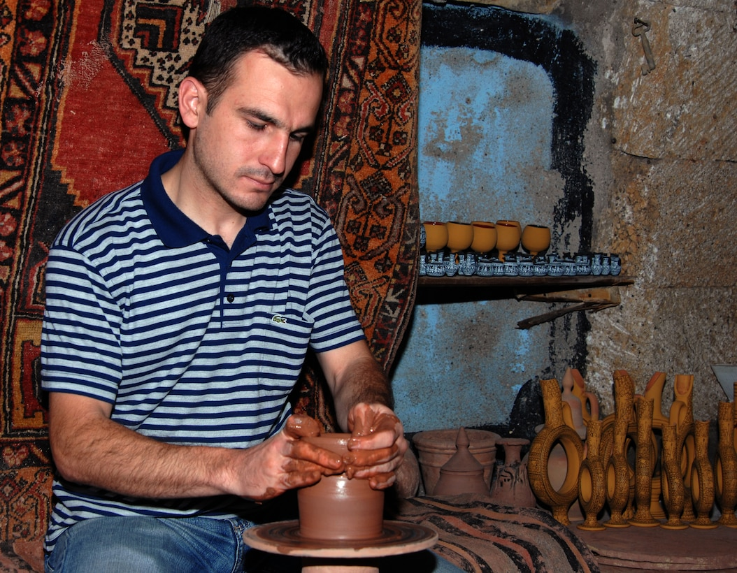 A Turkish artisan demonstrates how to sculpt a flower pot on a kick-style pottery wheel in an Avanos, Turkey, pottery shop. The town of Avanos is known for its terra-cotta products. Inside, the shop shelves were filled with clay jars, hand painted plates, wine carafes and goblets. (U.S. Air Force photo/Staff Sgt. Lauren Padden)