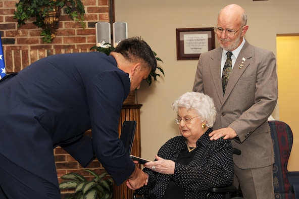 Col. Greg Otey, 19th Airlift Wing commander, presents  Louise Meroney and her son, Doug Meroney, the Prisoner of War medal on behalf of her late husband, Retired Col.  Virgil Meroney at the Trinity Village Retirement Community, Pine Bluff, Ark. Sept. 9. Colonel Meroney was captured and held as a POW in Germany during WW II for a year before escaping captivity near the Rhine River. (US Air Force photo by Senior Airman Jim Araos)