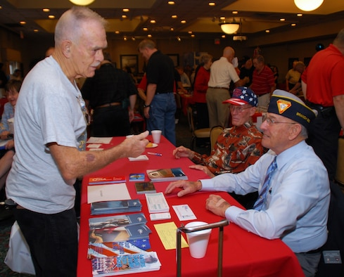 Retired Master Sgt. Jerry Hobson (right) and retired Chief Master Sgt. Silas Legrow, hand out brochures to retirees at the Fleet Reserve Association display table at the conference center during Retiree Appreciation Day, Sept. 12. Throughout the day, different vendors from around the area handed out free samples to retirees and informed them about their programs and organizations. (U.S. Air Force photo by Airman 1st Class Rochelle Clace)
