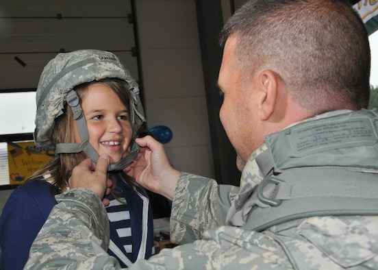 SPANGDAHLEM AIR BASE, Germany – Lt. Col. Gary Dawson, 606th Air Control Squadron director of operations, puts his helmet on his daughter Katie after returning from a four-month deployment to Kandahar, Afghanistan, Sept. 16.  About 60 members of the 606th ACS operated radar and communication for command and control for the 71st Expeditionary Air Control Squadron.  The unit also deployed 300 short tons of equipment to support air battle management operations and more than 13,000 sorties.  Approximately 30 other 606th ACS members also returned from a four-month deployment to southwest Asia in support of the 73rd EACS.  (U.S. Air Force photo/Airman 1st Class Nick Wilson)