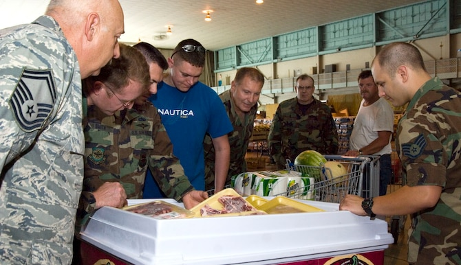 MARTINSBURG, W. VA., -- Members of the 167th Airlfit Wing, West Virginia Air National Guard, gather around a freezer ful of steaks on sale at the commissary On-Site Sale here July 10. Commissary workers from Andrews Air Force Base, Md., set up shop in a hangar at the unit and offered a variety of grocery, produce, and meat items for military members, retiree's and their families. Sales such as these are upcoming in the Northwest for 446th Airlift Wing Reservists to participate in. (U.S. Air Force photo/Master Sgt Emily Beightol-Deyerle)