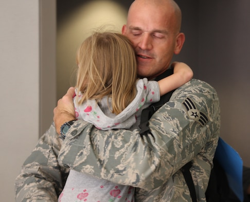WRIGHT-PATTERSON AFB, Ohio - Senior Airman Steven Sherman, 87th Aerial Port Squadron, hugs his daughter Amelia, upon his return from a six-month deployment to Balad Air Base, Iraq.  More than 50 squadron members deployed to Southwest Asia this spring and will be returning throughout the month of September. (Air Force photo/Maj, Cynthia Harris)