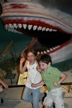 Military children Kaetlin Moffat, age 7, and Preston Russell, age 6,  jump with excitement in front of the a prehistoric shark exhibit, Megalodon, at the Museum of Ancient Life at Thanksgiving Point.  The children visited the museum as part of a free opportunity offered by Operation Military Kids this summer.