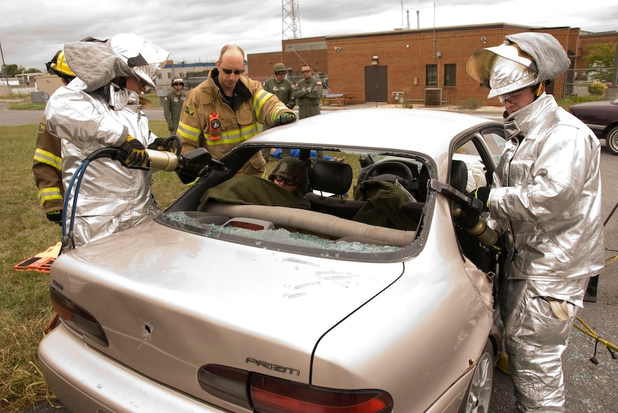 Staff Sgt. Joe Harper, center, and Tech. Sgt. Tara Bryant, inside car, both members of the 167th Aeromedical Evacuation Squadron, watch as 167th Fire Fighters Senior Airman Pierce Franklin and Senior Airman Mike Hurd use the Jaws of Life to remove the roof from a car during a training exercise at the 167th Airlift Wing, Martinsburg West Virginia, September 12, 2009. (U.S. Air Force Photo by Master Sgt Sean Brennan)