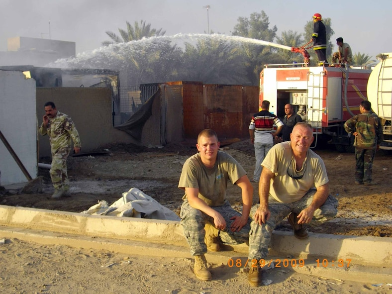 Senior Master Sgt. Judson Shull and Airman 1st Class Robert Bissett take a load off after fighting a fire in an Iraqi housing development  The two were off-base when a fire broke out in the nearby neighborhood.
