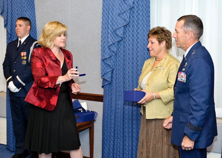 Sharon O'Malley Burg, daughter of the late Gen. Jerome and Diane O'Malley, presents Brig. Gen. Brett Williams with a set of brigadier general rank worn by General O'Malley as a special tribute to carry on the O'Malley legacy.  The presentation of the rank was part of a ceremony at the Pentagon Sept. 11, 2009, where General Williams and his wife, Marianne, were honored with the 2009 General and Mrs. Jerome O'Malley Award. The award was established after the O'Malleys, who were known for their leadership and contributions to Air Force families and communities, were killed in a plane crash in 1985.  (U.S. Air Force photo/Michael Pausic)