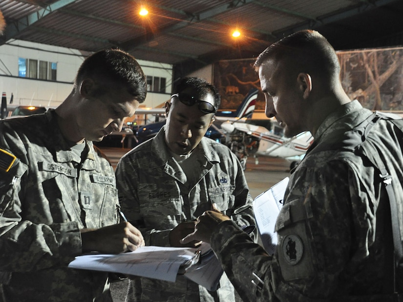 Just before dawn breaks at the Juan Santamaria International Airport in San Jose, Costa Rica, U.S. Army Capt. John Osterman, Air Force Tech. Sgt. Bill Flores, and Army Lt. Col. Curtis Anderson finalize the airlift plan for three Blackhawk helicopters supporting the Medical Readiness and Training Exercise in the remote Turrialba region of that Central American nation. (U.S. Air Force photo/Tech. Sgt. Mike Hammond)