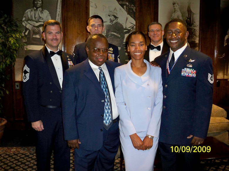 Tech. Sgt. Ramone Young, 566th Intelligence Squadron (right), poses with his family, retired Chief Master Sgt. William Young (front left) and Lori Young, and members of his squadron (back row, from left to right) Chief Master Sgt. Dale Armstrong, Master Sgt. Billy Poff and Master Sgt. Alan Weatherly. (Photo courtesy of Chief Master Sgt. Arleen Heath)