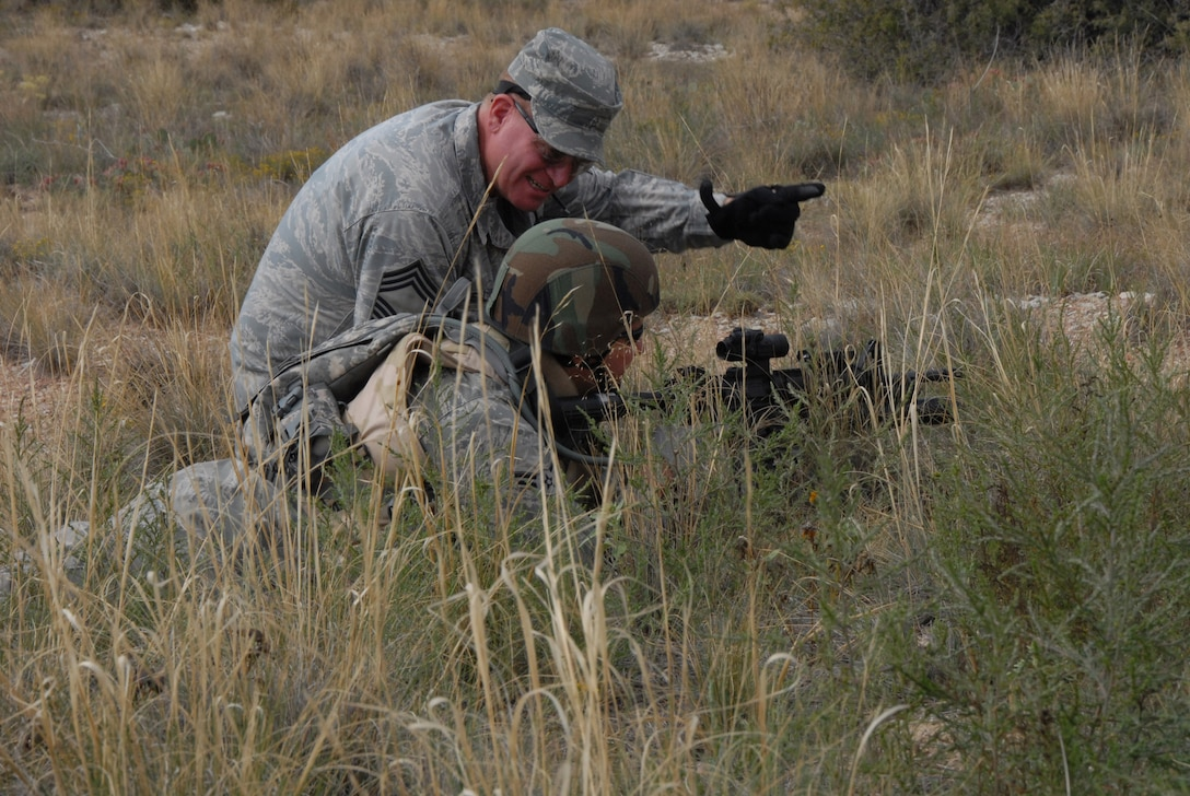 Chief Master Sgt. John Criswell of the 140th Security Forces Squadron instructs a young Airman on what to look for when watching an area of responsibility during a live fire training exercise Sept. 12, 2009 at Fort Carson, Colo. The Airman is attempting to see over the tall weeds that obstruct his view. During the training, 140th SFS cadre members passed on their knowledge and experience to guide the younger troops in order to make the training more efficient and practical for real-world scenarios. (Official U.S. Air Force photo by Staff Sgt. Armando Argiz, Colorado Air National Guard/Released)