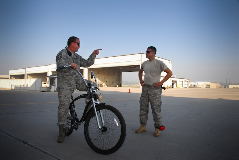 Senior Master Sgt. Al Dickrell and Tech Sgt. David Byzefski, F-16 crew chiefs with the 115th Aircraft Maintenance Squadron, discuss fl ightline operations. Sergeant Dickrell, a crew chief supervisor, sits atop a custom bike he personally bought to communicate with crew chiefs working the flightline here.