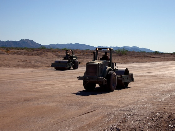 Two Marine Wing Support Squadron 374 heavy equipment operators smooth and compact an unmanned aircraft system runway at the Chocolate Mountain Aerial Gunnery Range in Calif., Sept. 21, 2009. The runway, which was the first built for UASs on the ranges of the Marine Corps Air Station in Yuma, Ariz., will open up new training opportunities for UASs visiting for the Weapons and Tactics Instructor course. Marine Unmanned Aerial Vehicle Squadron 1 will be the first squadron to use the runway during their training in the current WTI.