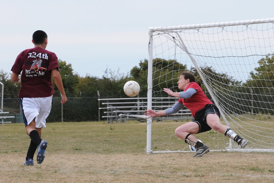 RAF MILDENHALL, England -- Goalkeeper Karen Wiekierak, 100th Operations Group player, dives to block a shot by an 100th Force Support Squadron player as it passes by defender Benito Carrasco, FSS, in intramural soccer play near the Hardstand Fitness Center here Sept. 21. The FSS put up a strong front with a full roster of seven players against OG's five player lineup. The lack of a full lineup contributed to OG's 1-4 loss. (U.S. Air Force photo/Senior Airman Thomas Trower)