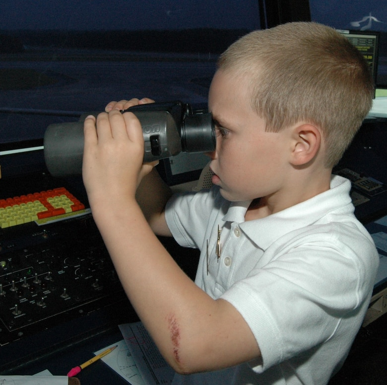 Jeremy Payne, 8, peers through binonculars while touring the Dobbins air traffic control tower Sept. 15. Jeremy was able to try his hand at flying a C-130 simulator, coordinating air traffic on the ATC simulator, received night-vision goggles training, attended pre-flight briefings and viewed a C-130 formation take off from the control tower.