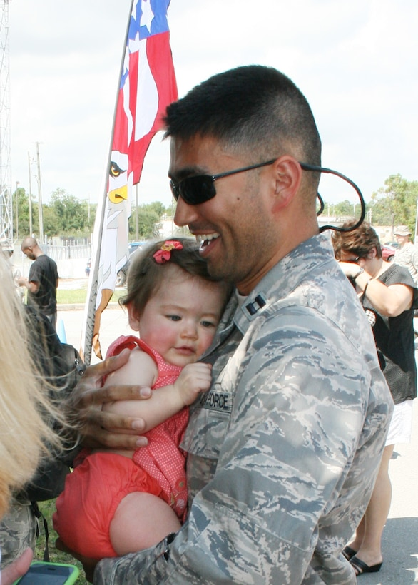 Captain Eric Bein, 728th Air Control Squadron air battle manager, receives a welcome home hug after returning from his first Operation Iraqi Freedom deployment with his unit Sept. 21. As one of the Air Combat Command's four unique Control and Reporting Centers, more than 150 members of the 728th ACS provided command and control of joint air operations using surveillance, identification, weapons control, battle management and theater data links while overseas. (U.S. Air Force photo/2nd Lt. Andrew Caulk)