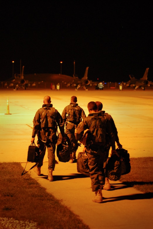 Pilots from the 115th Fighter Wing step to their F-16 Fighting Falcons after receiving a pre-departure briefling for their flight to Iraq, in support of Operation Iraqi Freedom, Sept 22.  The 115th launched 14 F-16s early Tuesday morning as a part of the Wing's scheduled Air Expeditionary Force rotation that began last week when approximately 200 Airmen deployed to theater.  (U.S. Air Force photo by Staff Sgt. Ashley Bell)
