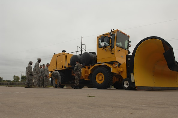 WHITEMAN AIR FORCE BASE, Mo. -- Staff Sgt. Edwin Salgado, 509th Civil Engineer Squadron, gives an equipment familiarization brief on a Rollover Plow to members of the 509th CES. The Rollover Plow is used throughout the winter months to make flight operations possible. (U.S. Air Force photo/Senior Airman Jessica Snow)