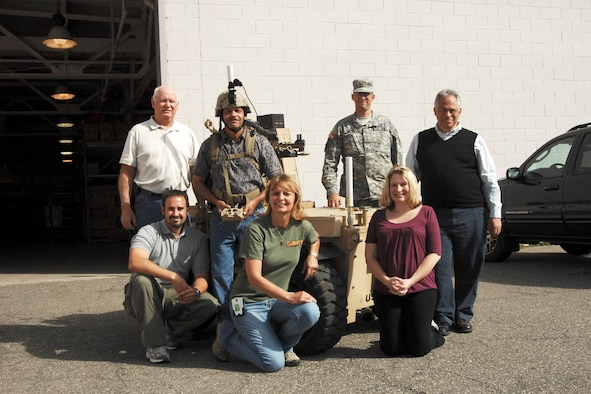 Personnel involved with the testing of the IbisTek wireless data link radio at Selfridge Air National Guard Base, Mich., last week, gather around the Gladiator robot.  The unique joint nature of the base in the northern suburbs of the metro-Detroit area, brought together many parts of the Army and the Air Force to create a cost-saving test environment for the radio which promised increased range for use on an Unmanned Ground Vehicle.  In this photo (left to right, starting back row), Mr. Greg Hudson, robot technician; JS RPO; Mr. Randall Ponder, engineering technician, JS RPO; the Gladiator Robot; Major Kevin Schrock, assistant manager, product APM maneuver system; Mr. Samuel Pirrone, radio frequency engineer; (front row) Mr. Robert Rappold, engineering team lead, Small Unmanned Ground Vehicles; Ms. Valerie Bolhouse, systems engineer; and Ms. Shanna Render, TARDEC Gladiator project manager.